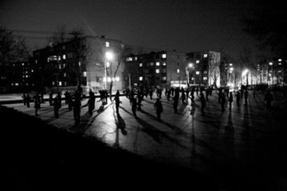 市民在双潭公园广场上借着路灯的光亮跳舞健身.