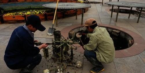 淇滨区新世纪广场上几名工人正在将地下的喷泉设备搬到地面上